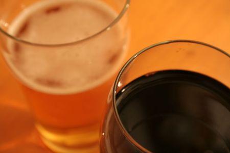 pilsner: Una pinta de cerveza y un vaso de vino tinto en contra de un conjunto de granos de mesa de madera.