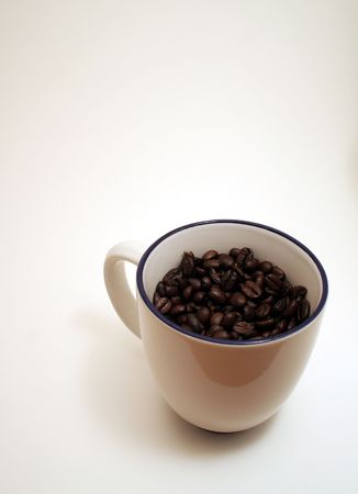caffiene: A coffee cup filled with fresh coffee beans. Stock Photo