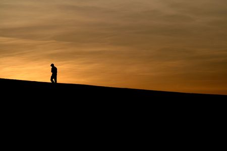A distraught boy walks off toward the sun.
