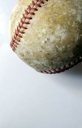 Closeup of a battered old baseball against a white background. photo