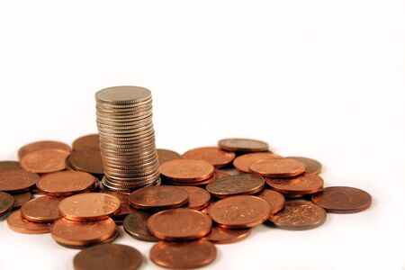 A single stack of coins rising above a bunch of pennies. Imagens