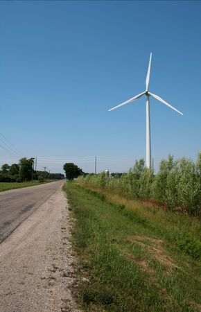 A windmill power generator on the side of the road in the middle of farm land. photo