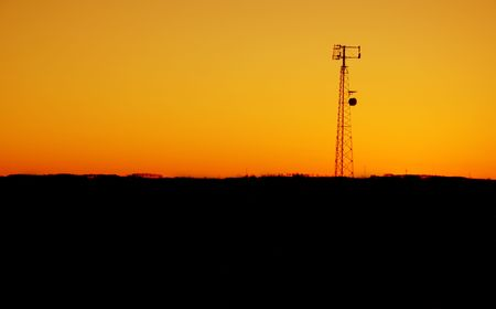 impart: A cell phone tower silhouette in the sunset Stock Photo
