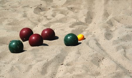 precisely: A game of bocce ball played in sand, at the beach. Stock Photo