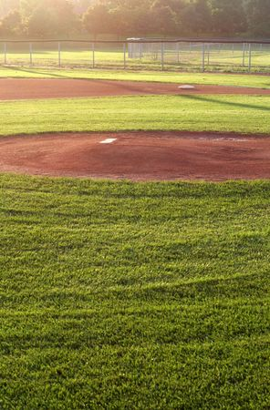 fence: A baseball field cast in early morning light.