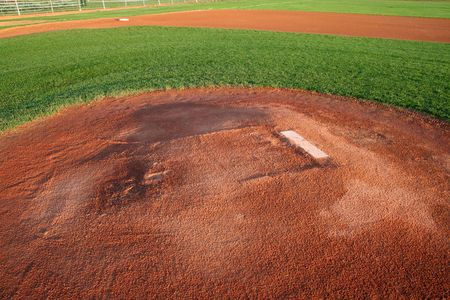 A shot of a baseball field from right behind the pitchers mound. photo