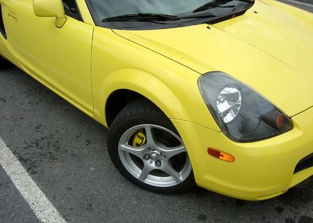 A yellow sports car sitting in a parking space. photo