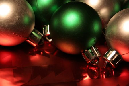 red metallic: Green and silver Christmas ballsbaubles resting on red metallic wrapping paper. Stock Photo
