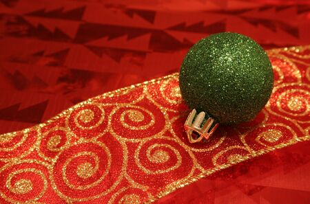 A sparkling green christmas ball ornament resting on a ribbon.  Stock Photo