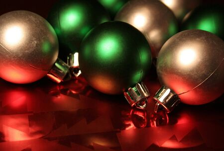Green and silver Christmas balls/baubles resting on red metallic wrapping paper.