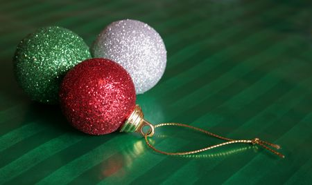 Three shiny Christmas baubles sitting on green wrapping paper. photo