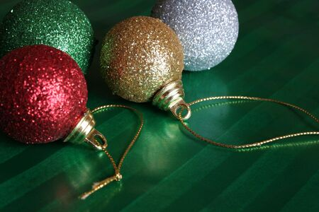 Four shiny christmas balls resting on green wrapping paper. Stock Photo
