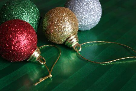 Quatre boules brillantes de Noël se reposant sur le papier d'emballage vert. Banque d'images - 598208
