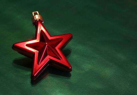 A shiny red Christmas star ornament sitting on green wrapping paper.