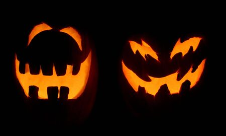 Two carved pumpkins glow on Halloween night.