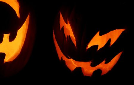 A closeup shot of two carved pumpkins on Halloween night. photo