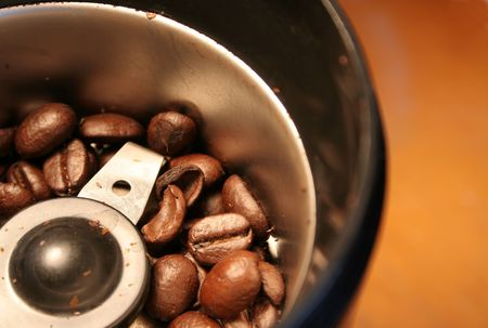 caffiene: Fresh coffee beans sitting in a coffee grinder.