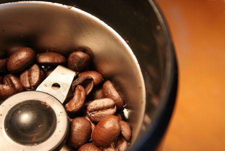 grinder: Fresh granos de caf� sentado en un molino de caf�.