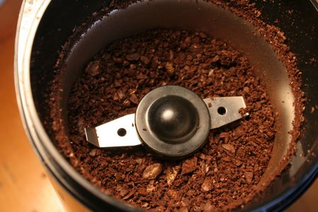 caffiene: Coffee grinds sitting in the coffee grinder.