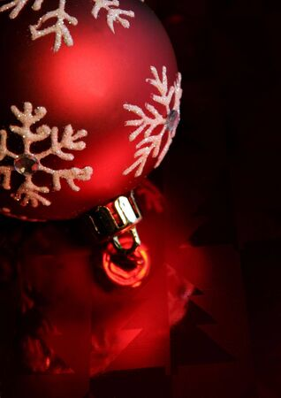 A single red christmas ornament illuminated on glossy red paper. photo