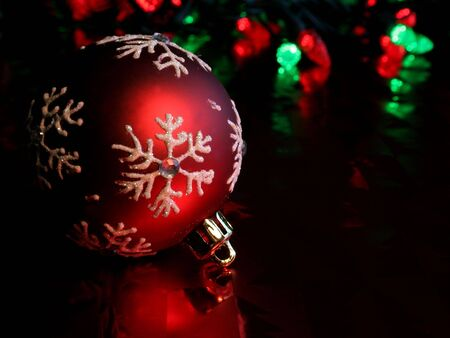 A single red christmas ornament illuminated on glossy red paper. Stock Photo