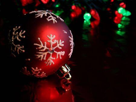 Un ornement rouge simple de Noël illuminé sur le papier rouge glacé. Banque d'images - 631155