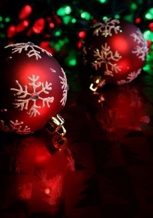 Two red christmas baubles illuminated on glossy red paper.