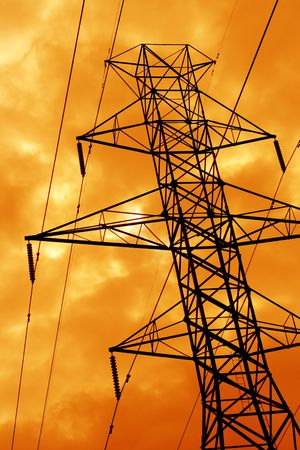 The silhouette of a power line tower against an ominous orange sky.