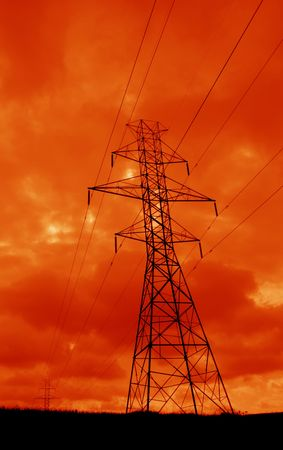 ominous: The silhouette of a power lines and towers against an ominous orange sky.  Stock Photo