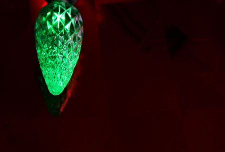 A single green led christmas light resting on a glossy red