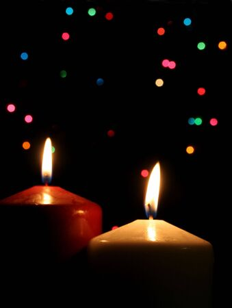 Two Christmas candles up close, with festive lights in the background. Imagens