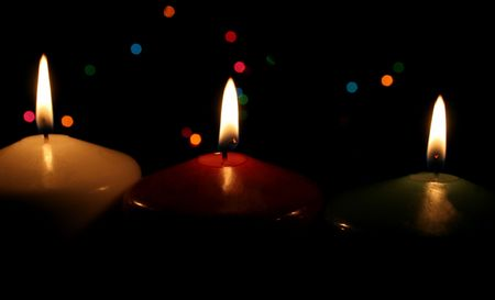 Three Christmas candles up close, with festive lights in the background. Stock Photo - 661515