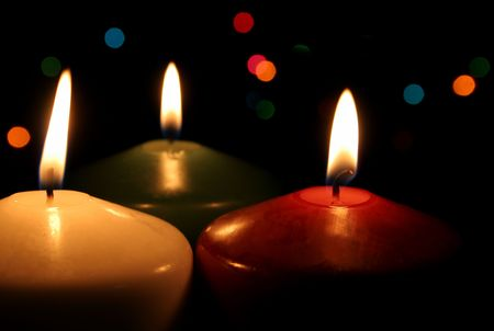 Three Christmas candles up close, with festive lights in the background.