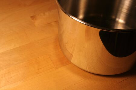 A metallic cooking pot sitting on a wood table. photo