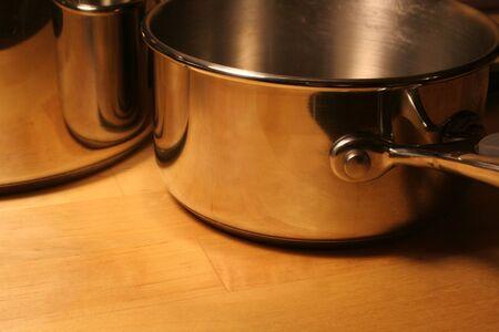 Metallic pots sitting on a wooden table. photo