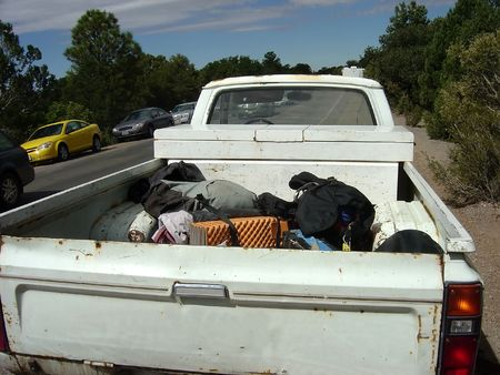 wheel truck: A beat up white pick up truck with hiking gear piled in the back. Stock Photo
