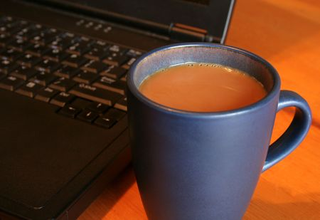 A fresh cup of sitting on wood table in front of a laptop.