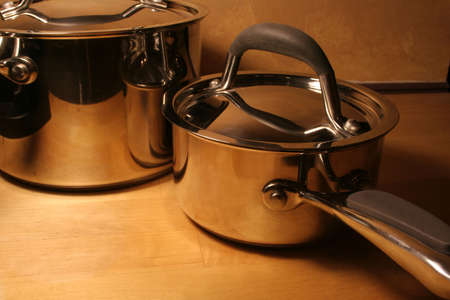 percolate: Metallic pots sitting on a wooden table. Stock Photo