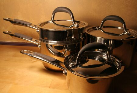Pots and pans sitting on a wooden tables. Stock Photo