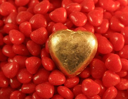 foil: Golden Foil wrapped chocolate heart set against cinnamon hearts.