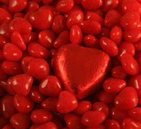 foil: Red Foil wrapped chocolate heart set against cinnamon hearts.