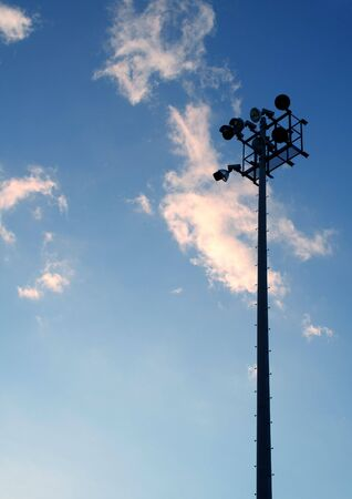 The silhouette of stadium light stand set against a blue sky with white clouds.