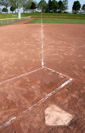 campo de beisbol: Un gran angular de tiro mirando hacia abajo en la l�nea izquierda del campo de la placa y la caja de bateadores.