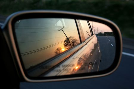 A sunset in the rearview mirror of car as a races down the road. Stock Photo - 1078599