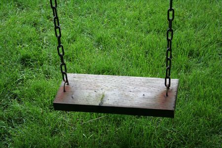 A closeup of an old wooden swing sitting above lush green grass. photo