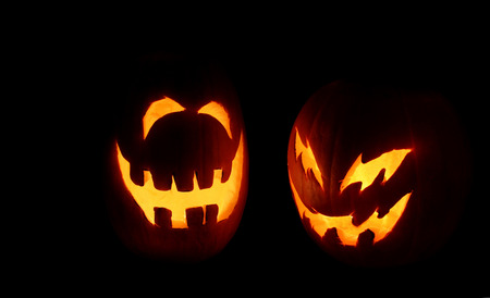 Two carved pumpkins glow on Halloween night. photo