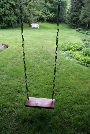 An old wooden swing sitting in a lush backyard.