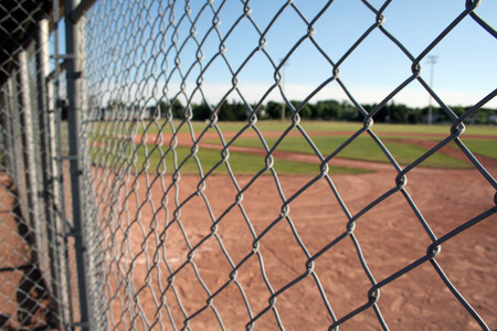 A view from behind the fence at a small baseball field. Stock Photo