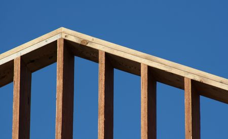 The crest of the wooden frame of a new house set against the blue sky.