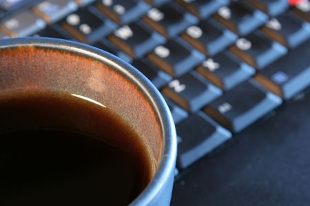 energy work: A fresh cup of sitting on in front of a laptop.